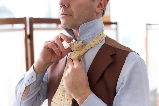 Man knoopt zijn stropdas tijdens het aankleden
