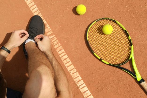 Man knoopt zijn veters vast op gravel met racket en ballen