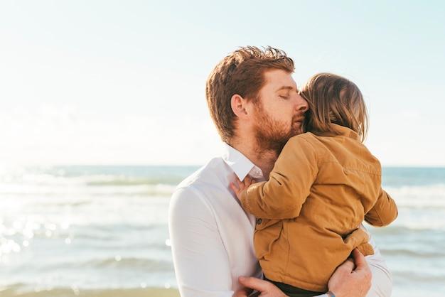 Man knuffelen kind aan kust
