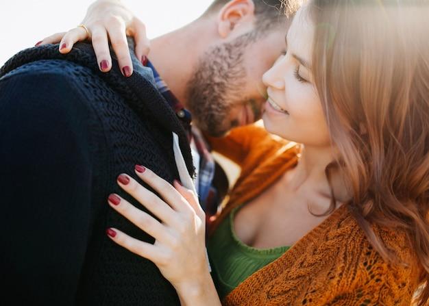 Man knuffelen vrouw, glimlachend, buitenshuis.