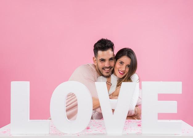Man knuffelen vrouw in de buurt van liefde inscriptie