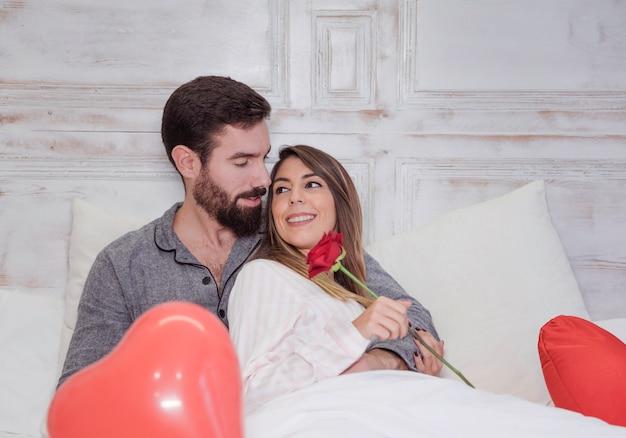 Man knuffelen vrouw met roos op bed
