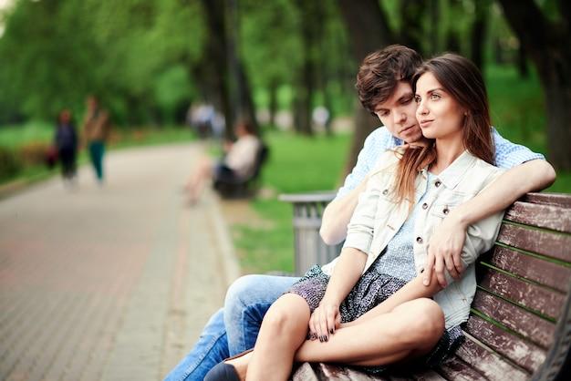 Man knuffelen zijn vriendin zittend op een bankje in het park in de zomer