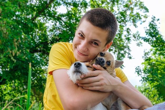 Man knuffelt twee honden en lacht vrolijk in het park