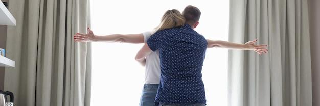 Man knuffelt zachtjes een vrouw in hotelkamer naast koffer