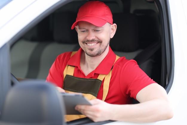 Man koerier in uniform zit aan het stuur van de auto met digitale tablet in zijn handen