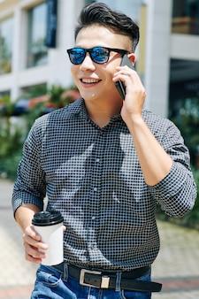 Man koffie drinken en bellen op telefoon