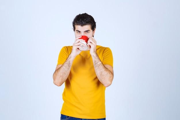 Man koffie drinken uit zijn rode mok.