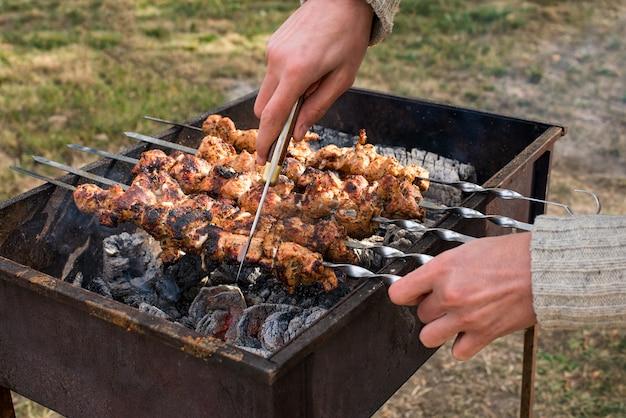 Man koken, alleen handen, hij snijdt vlees of biefstuk voor een gerecht. heerlijk gegrild vlees op de grill. barbecue weekend. selectieve aandacht.