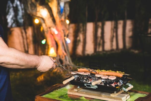Man koken bij de barbecue