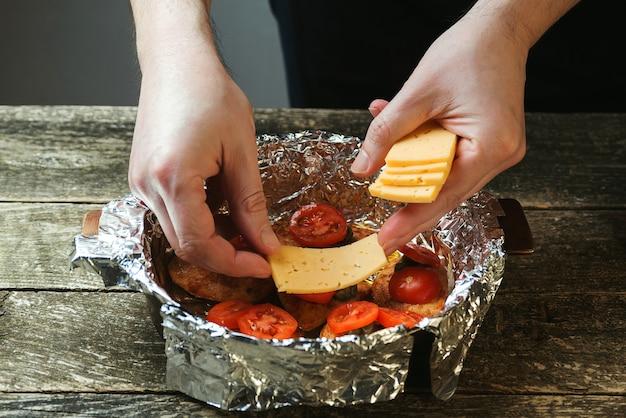 Man koken kipfilet met kappertjes, tomaten en kaas. snel recept voor een gerecht.