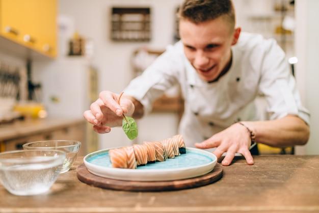 Man koken sushi rolt op houten tafel, japanse keuken voorbereidingsproces.