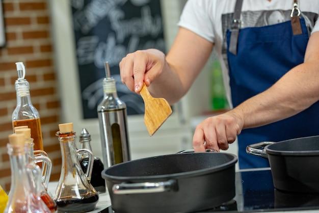 Man kookt vlees in een koekenpan. hand met spatel om de pan vol vlees te roeren.
