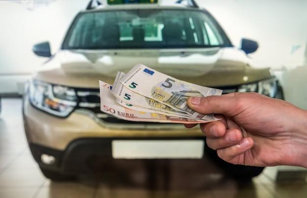 Man koopt nieuwe auto die eurobankbiljetten geeft. financiering aankoop concept
