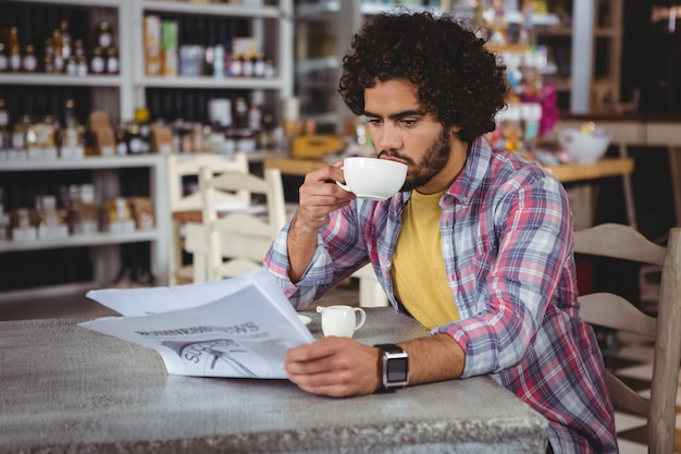 Man krant lezen terwijl het hebben van koffie