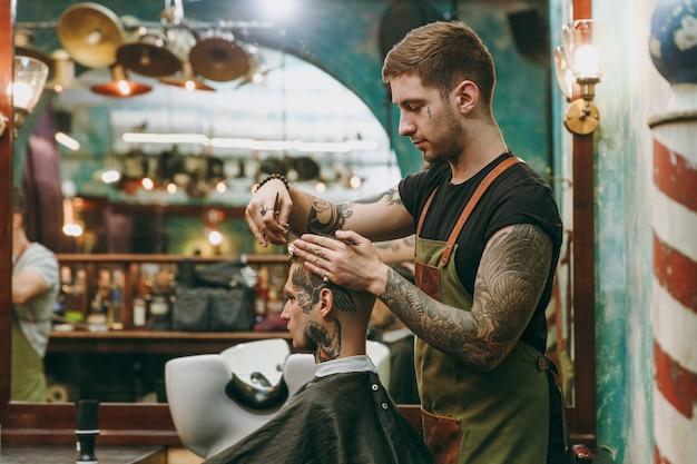 Man krijgt trendy kapsel bij kapperszaak. de mannelijke kapper in tatoeages ten dienste van de klant.