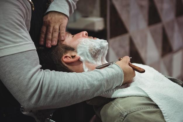 Man krijgt zijn baard geschoren met een scheermes