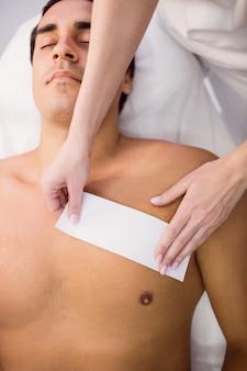 Man krijgt zijn borst gewaxt met wax strip