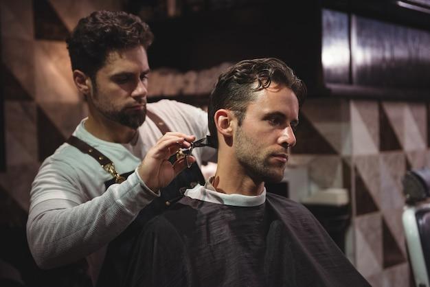 Man krijgt zijn haar bijgesneden met een schaar