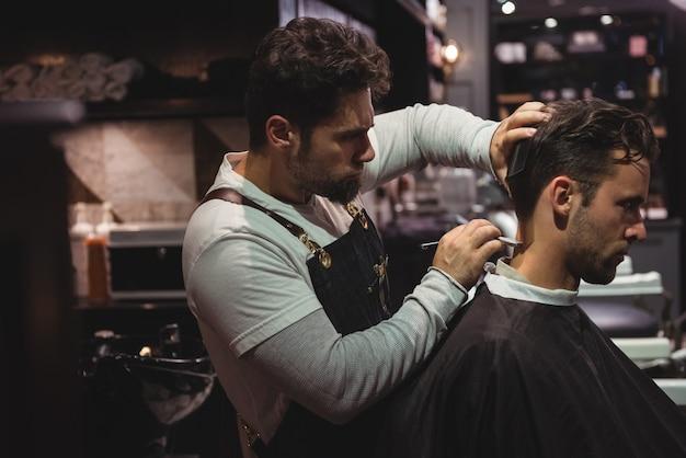 Man krijgt zijn haar bijgesneden met een scheermes