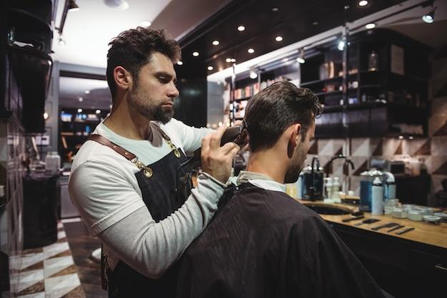 Man krijgt zijn haar bijgesneden met trimmer