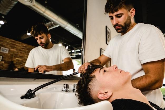 Man krijgt zijn haar gewassen door professionele kapper
