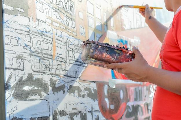 Man kunstenaar schilderij aan de muur en verf lade in de hand te houden