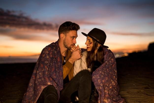 Man kussende hand van vrouw op het zitten op overzeese kust
