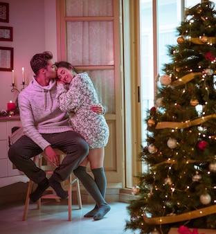 Man kussende vrouw op het voorhoofd in de buurt van de kerstboom