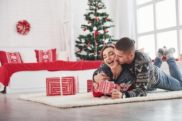 Man kust zijn vrouw op de wang. mooie jonge paar liggend op de woonkamer met groene boom