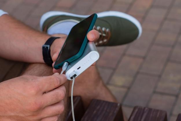 Man laadt een smartphone op met een powerbank in de hand. draagbare oplader voor het opladen van gadgets.