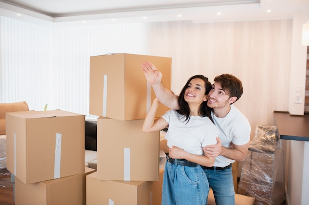 Man laat zijn vrouw een nieuw appartement zien. een jong getrouwd stel in de woonkamer in het huis staat bij uitgepakte dozen. ze zijn blij met een nieuw huis. verhuizen, kopen van een huis, appartement concept.