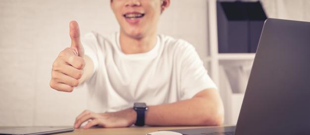Man lachend gezicht en het tonen van duimen omhoog of zoals zittend op een bureau, succesvolle zaken.
