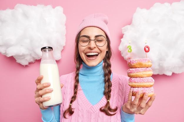 Man lacht en heeft plezier poseert met heerlijke donuts en melk heeft zoetekauw viert verjaardag draagt hoed coltrui met vest ronde bril poseert rond witte wolken