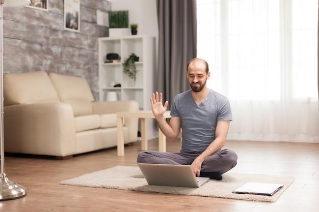 Man lacht en zwaait tijdens een videoconferentie op laptop zittend op tapijt.