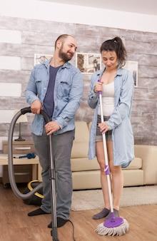 Man lacht naar vrouw terwijl hij samen het huis schoonmaakt