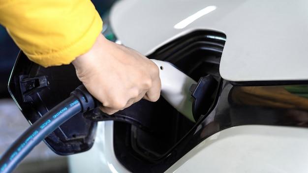 Man lader aansluiten op een witte elektrische auto