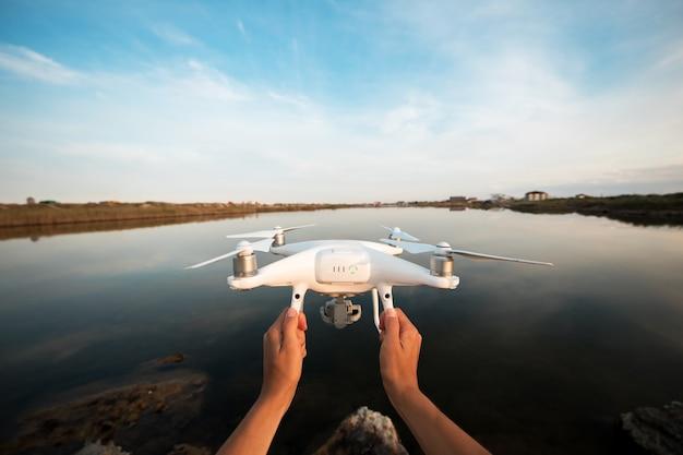 Man lanceert drone uit handen in de buurt van rivier