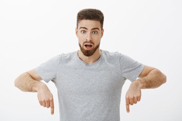 Man leerde hoe gig-economie werkt door verbaasd en geïntrigeerd te poseren in een grijs t-shirt en geschokt te kijken met geopende mond naar beneden wijzend ondervraagd en verrast over witte muur
