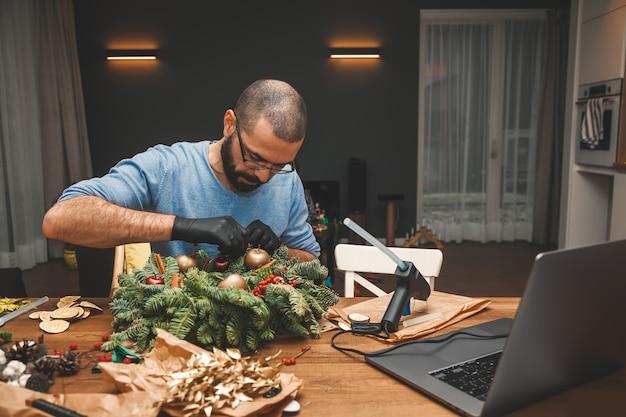 Man leert een kerstkrans te versieren, kijk online naar les kerstboomkransdecoratie