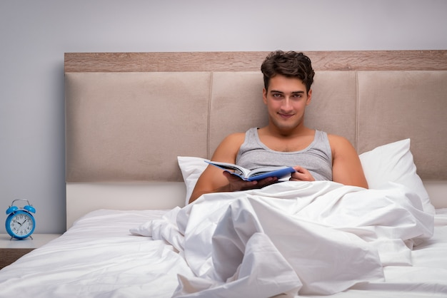 Man leesboek in het bed