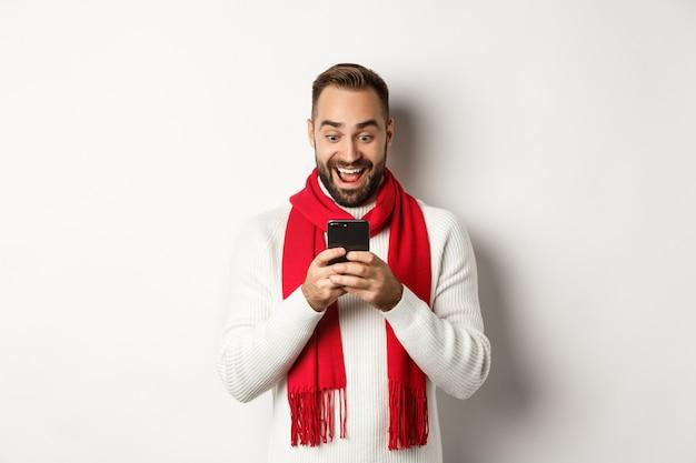 Man leest berichten op mobiele telefoon en ziet er gelukkig uit, staande in wintertrui en rode sjaal, witte achtergrond.