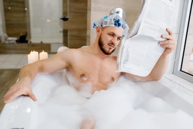 Man leest krant in bad met schuim, ochtendhygiëne. mannelijke persoon ontspannen in de procedures voor badkamer-, huid- en lichaamsbehandelingen
