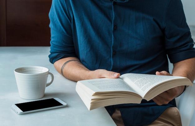 Man leest met koffie