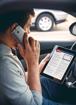 Man leest nieuws autorijden met een tablet in de hand, praten op mobiel