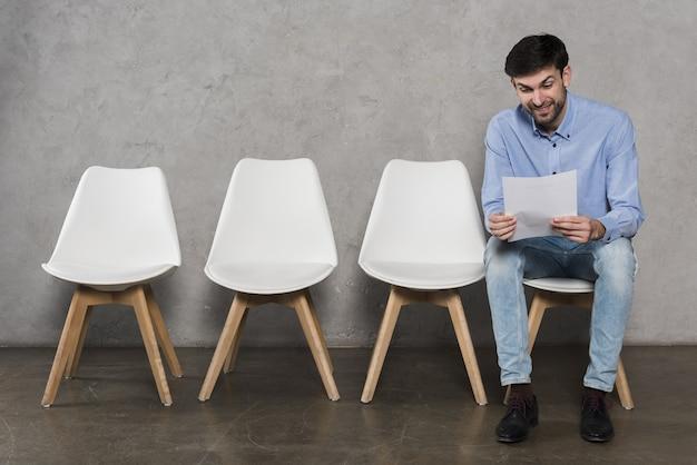 Man leest zijn cv voordat hij zijn sollicitatiegesprek heeft