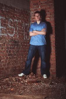 Man leunend op een bakstenen muur in verlaten onafgewerkt huis