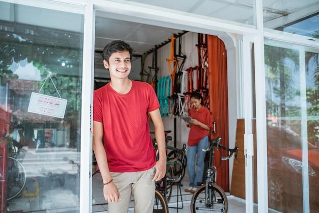 Man leunt voor de glazen deur van een winkel met een vrouw op de achtergrond