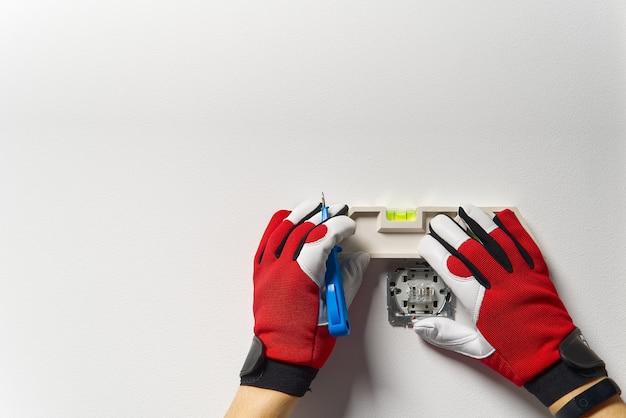 Man lichtschakelaar installeren na renovatie van het huis. elektricien lichtschakelaar installeren op geschilderde muur met schroevendraaier