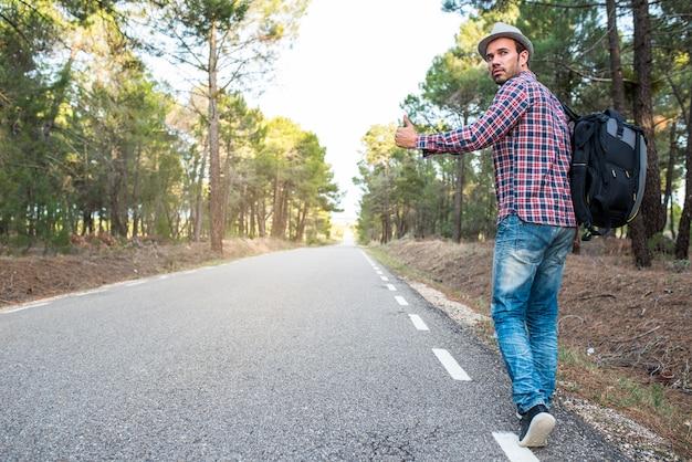 Man liften met duimen omhoog in een landelijke weg